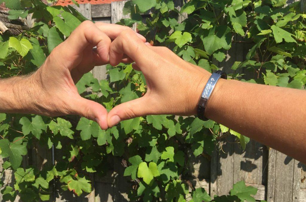 Twee handen maken een hartje, armband met SGVOPJ erop